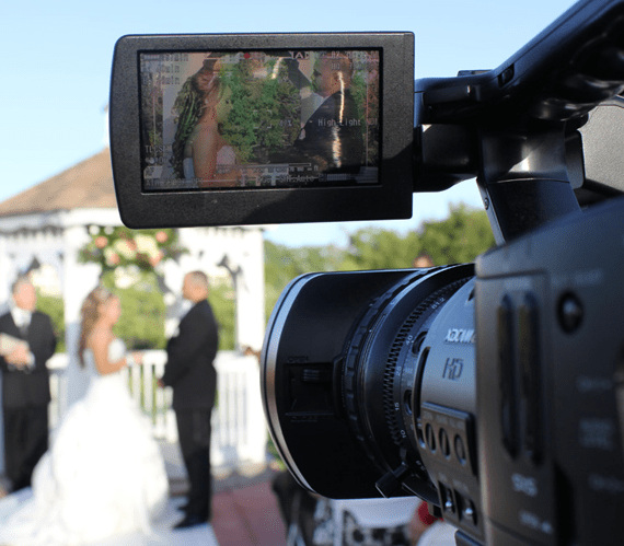 JC Pro- A photo of a video camera lens taking a video of a couple while they are getting married
